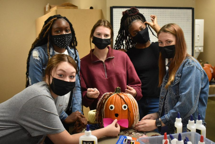 EHS students decorating their pumpkin with crafting materials.